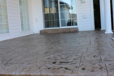 Dark brown paver style stamped concrete patio with a polished finish.