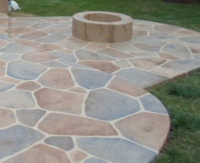 Decorative stone stamped concrete patio with a built in fire pit in Danbury.
