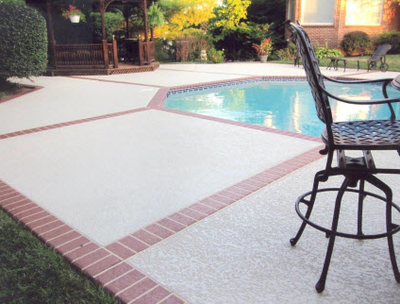 Textured concrete pool deck with brick edging and details.