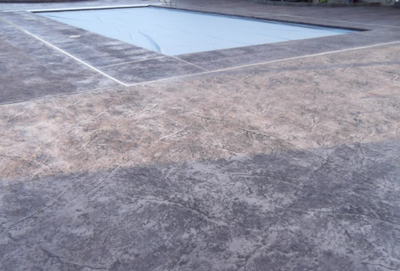 Stamped gray concrete textured around built in pool.