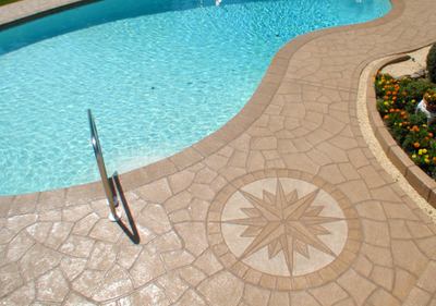 Brown decorative concrete with compass detail around built in pool.