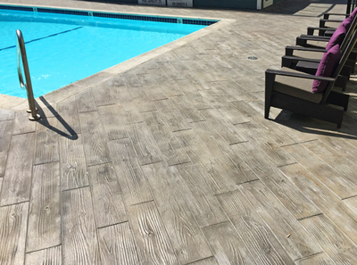 Pool deck with stamped concrete made to look like wood planks.