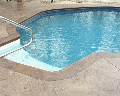 Brown stained and textured concrete around outdoor pool.
