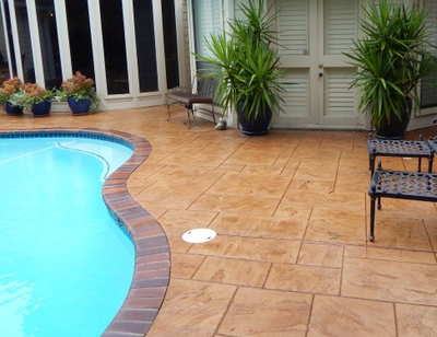 Brown stained and stamped concrete pool deck with brick stamped edging.