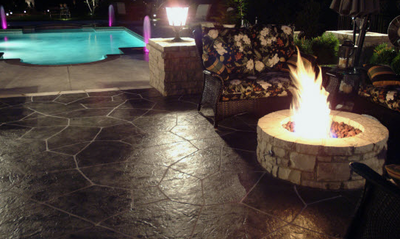 Dark brown stone stamped concrete patio adjacent to a built in pool.